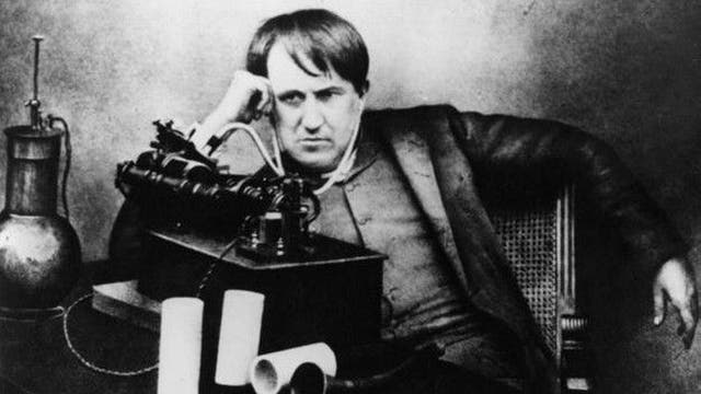El científico Thomas Edison escucha su fonógrafo a través de un primitivo auricular