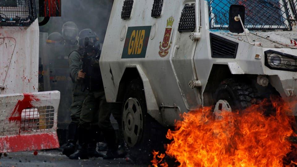 Los manifestantes incendian vehículos de la policía. Foto: Reuters / Carlos Garcia Rawlins