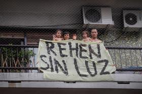 Una pareja con sus dos hijos y un mensaje claro desde el balcón de su departamento del 5° piso en la avenida Rivadavia al 5900, en Caballito