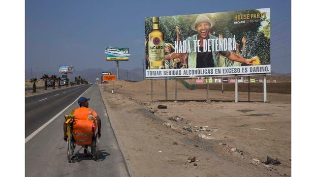 José Suárez, de Cúcuta, Colombia, mueve su silla de ruedas a lo largo de la Carretera Panamericana bordeada de carteles publicitarios de ron, lotería y nueces mixtas, al sur de Lima