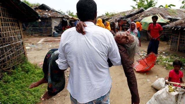 Un hombre lleva a una mujer refugiada de Rohingya desde la orilla luego de cruzar la frontera de Bangladesh-Myanmar en un barco a través de la bahía de Bengala