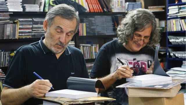Ernesto Gontrán Castrillón y Sergio Coscia, los autores del libro, escriben la dedicatoria en ejemplares llevados por varios habitués de la disquería Mondo Rabioso, donde se conocieron