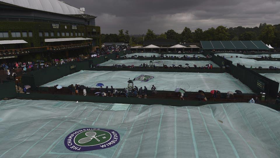 Una lona cubre la pista para protegerla de la lluvia que, una vez más, obliga a retrasar los partidos, en el quinto día del Torneo de tenis de Wimbledon hoy, 1 de julio de 2016.. Foto: EFE / ANDY RAIN