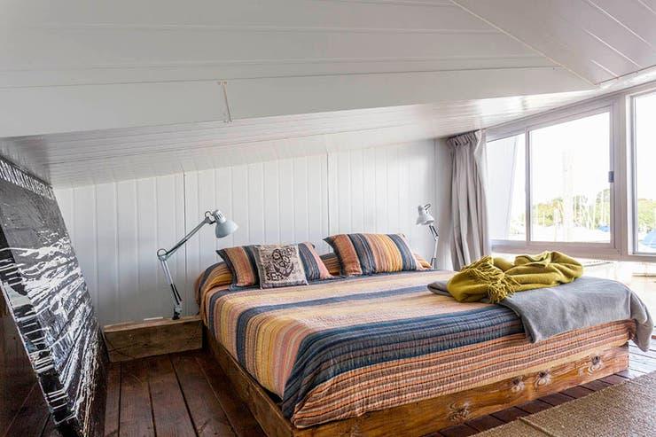 La base de la cama se recubrió en madera rústica, que continúa en las mesas de luz. Apoyadas, dos lámparas móviles