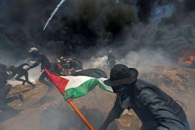 Manifestantes palestinos huyen del fuego israelí y del gas lacrimógeno durante la protesta contra el traslado de la embajada de EE. UU. A Jerusalén