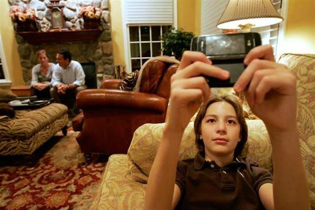 Dylan Herina, de 13, manda mensajes de texto, con sus padres Beth y Peter de fondo. Las nuevas tecnologías plantearon desafíos a las normas de convivencia familiar.