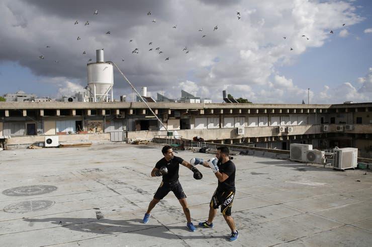 Los instructores Doron Turgeman, de 35 años, y Michael Alimelech, de 26, entrenan en la azotea del edificio en el que imparten cursos, como parte de su Krav Maga, una técnica de autodefensa israelí, en el barrio de Givatayim.