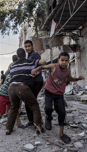 Un grupo de palestinos busca refugio de los misiles
