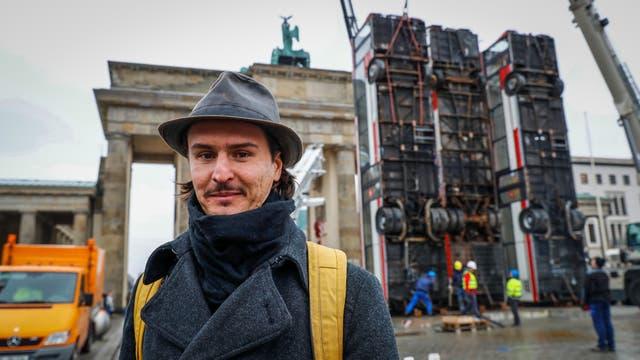 El artista sirio-alemán Manaf Halbouni delante de su obra