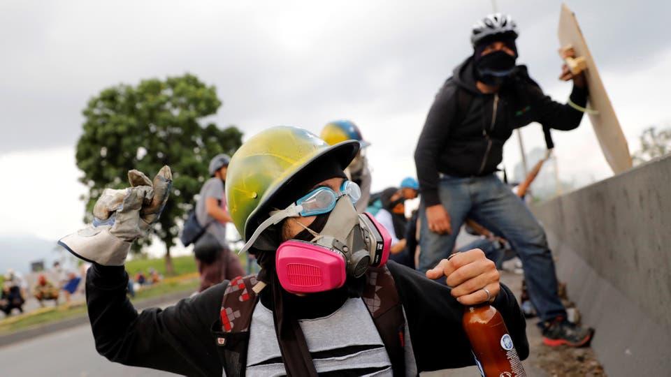 Los manifestantes opositores lanzan piedras a la policía. Foto: Reuters / Carlos Garcia Rawlins