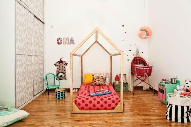 Una original cama de madera sin patas (que un carpintero hizo realidad) con un acolchado de gabardina de algodón rosa con lunares colorados y almohadones rosa chicle y crudo, con lunares azules, amarillo y modelo 'Blancanieves' (todo Tiendafan).  /Magalí Saberian