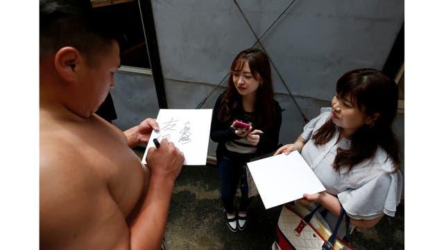El mongol, Tomozuna Oyakata, o maestro del establo de Tomozuna, firma autógrafos para sus fans después de una sesión de entrenamiento en el templo Ganjoji Yakushido en Nagoya