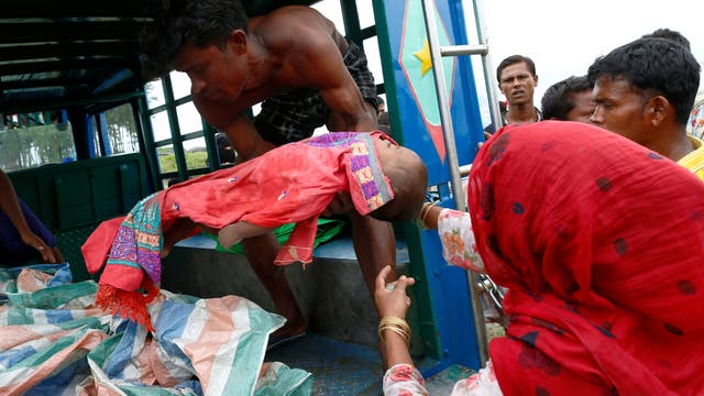 Una mujer refugiada Rohingya carga el cuerpo de su hijo que murió después del naufragio del barco en el que viajaba en la Bahía de Bengala