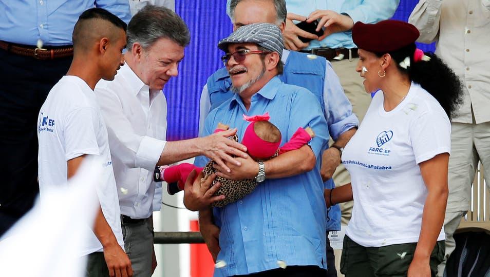 El líder rebelde de las FARC, Rodrigo Londono, sostiene un bebé al lado del presidente colombiano Juan Manuel Santos. Foto: Reuters / Jaime Saldarriaga