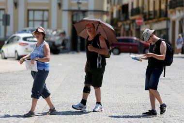 Las personas se cubren del sol en una plaza en Ronda, Málaga