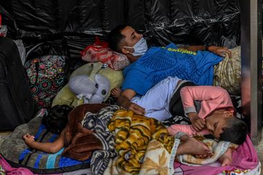 Migrantes venezolanos que desean regresar a su país debido a la pandemia del coronavirus, acampan frente a la terminal de autobuses en Medellín, Colombia, el 19 de mayo de 2020