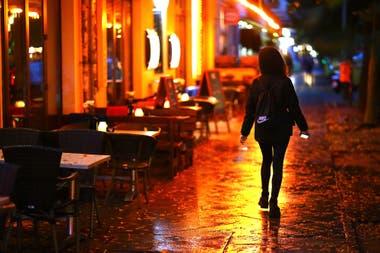 Una mujer camina por una zona de bares con mesas vacías antes del toque de queda nocturno, por la pandemia de coronavirus, en Berlín, Alemania