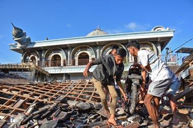 Los residentes rescatan de sus viviendas todo lo que no haya sido destruido por el terremoto