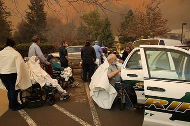 Trabajadores del hospital y socorristas evacuan a los pacientes del hospital Feather River en Paradise, California.