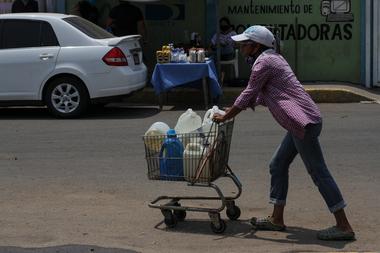 Una mujer empuja un carrito cargado con botellas de agua recolectadas de un grifo improvisado en una calle de Maracaibo, Venezuela, el 25 de mayo de 2020 durante la pandemia del coronavirus