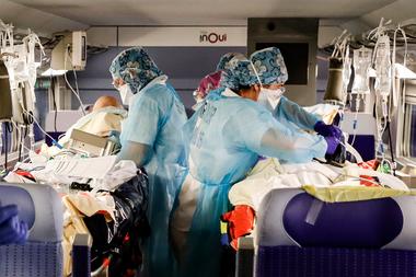 En esta foto de archivo tomada el 1 de abril de 2020, el personal médico instala pacientes infectados con coronavirus a bordo de un tren de alta velocidad TGV en la estación de trenes Gare dAusterlitz en París