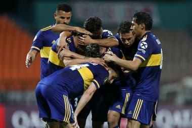 Los jugadores de Boca abrazan a Eduardo Salvio, que acaba de anotar un gol que vale tres puntos: el equipo xeneize venció 1-0 al DIM en Medellín (Colombia).
