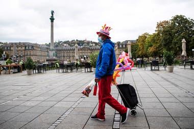 Un artista de globos camina por la Schlossplatz vacía, con una máscara facial, en Stuttgart, Alemania