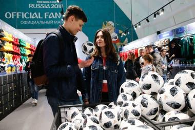 Visitantes recien llegados en la tienda oficial del FIFA Fan Fest en Moscú, con la pelota mundialista