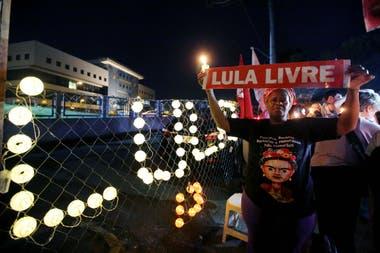 """Una mujer coloca un letrero luminoso que reza """"Lula libre"""" afuera de la Superintendencia de la Polícia Federal, en Curitiba"""