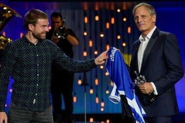 El actor y cineasta Viggo Mortensen recibe una camiseta de fútbol con su nombre de manos del futbolista Asier Illaramendi, tras recibir el Premio Donostia