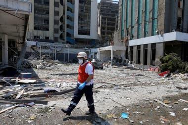Un miembro de la Cruz Roja recorre una zona destruida por la explosión de ayer, en Beirut, Líbano