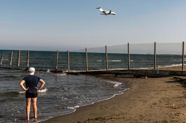 Una persona se para en la orilla del mar mientras un avión desciende hacia el Aeropuerto Internacional de Larnaca de Chipre