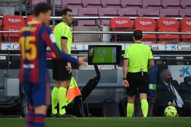 El árbitro español Juan Martínez Munuera (R) revisa el VAR: la jugada que decantó el clásico.