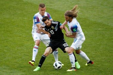 Messi pelea la pelota con los jugadores Birkir Bjarnason y Alfred Finnbogason