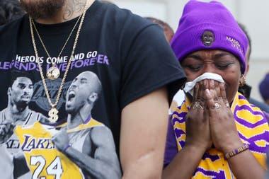 """Una simpatizante parece rezar por Kobe Bryant, que estuvo omnipresente en la vestimenta de la gente: """"Los héroes van y vienen. Las leyendas son viven para siempre"""", afirma la frase."""