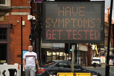 Los peatones pasan en frente de un tablero electrónico que insta someterse a un test si tienen síntomas de Covid-19 en Bolton, noroeste de Inglaterra, el 9 de septiembre de 2020