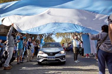 Los autos pasan por un túnel hecho con una bandera, en Mendoza