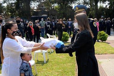 La ministra Sabina Frederick entregó la bandera argentina a la esposa del inspector Juan Pablo Roldan