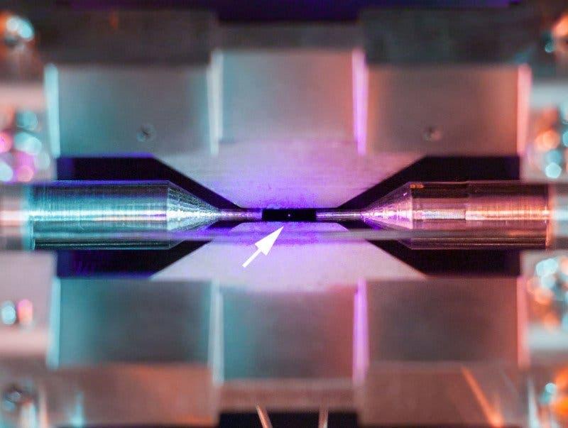 La flecha indica dónde está el reflejo generado por el rebote del láser en el átomo; la distancia entre los electrodos es de 2 milímetros