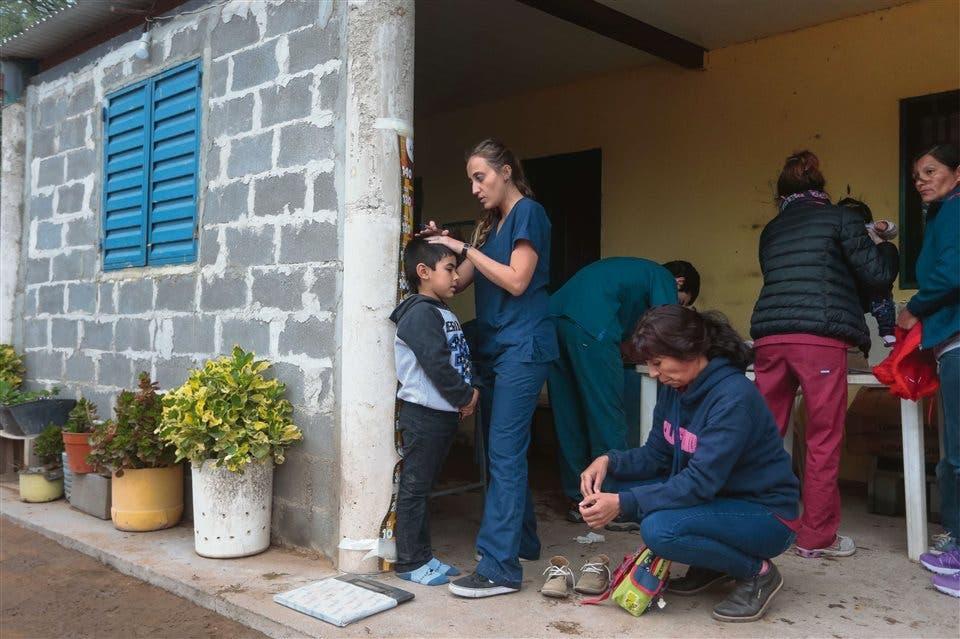 Control de talla. Una de las voluntarias del equipo médico toma las medidas de un niño frente a la casa de María Rodríguez. El problema de la malnutrición se refleja en la altura y el peso de los chicos