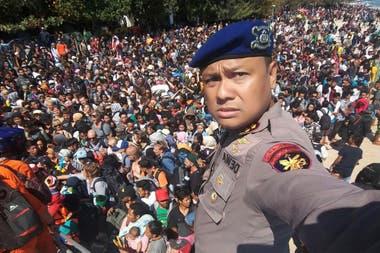 El jefe de la policía de Lombok, Dewa Wijaya, se toma una fotografía frente a cientos de personas que intentan abandonar Gili Trawangan, al norte de la vecina La isla de Lombok