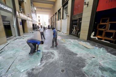 """Trabajadores limpian los escombros en el distrito comercial """"Souks"""" de Beirut"""