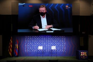 El entrenador del Barcelona, Ronald Koeman, firma su contrato. Suárez dice que todavía no se comunicaron.