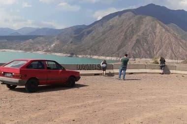 La mujer se inclina a pintar mientras un hombre mira su accionar unos metros más atrás, con sus brazos cruzados