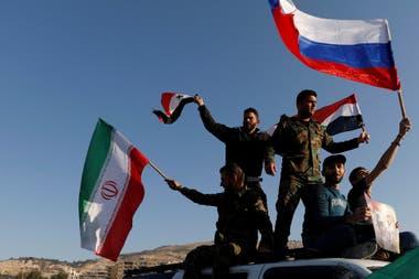 Soldados sirios agitan las banderas de Siria, Iran y Rusia durante una protesta contra los ataques aéreos de Estados Unidos