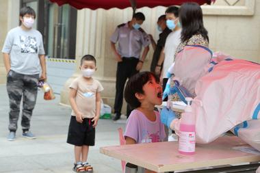 Un trabajador de salud realiza una prueba de coronavirus en un niño en un centro de pruebas improvisado en Dalian, en la provincia de Liaoning, noreste de China, el 27 de julio de 2020