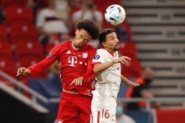 Leroy Sane y Jesús Navas luchan por la pelota en Sevilla-Bayern Munich