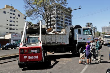 Una pala mecánica carga basura en un camión.