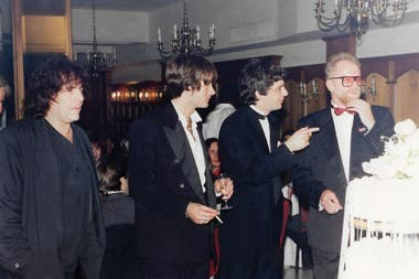 Pappo, Memi, Juanse y el productor de los Stones, Andew Oldham, rodean la torta de casamiento del cantante, en 1994