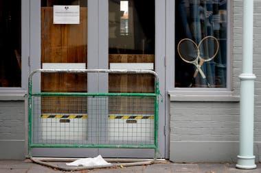 Raquetas de tenis en la vidriera de un pub cerrado de Wimbledon; la cancelación del torneo es un golpe para los comercios.